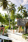 INDONESIA, Mentawai Islands, men and woman walking outside Kandui Resort