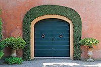 Stout double doors framed by box hedging in the shape of an arch herald the entrance to the garden