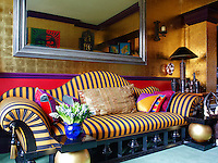 A theatrical striped banquette designed by Anthony Collett dominates one of the gilded walls in the living room