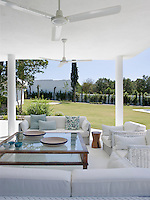 A shady terrace furnished with chic and comfortable white rattan seating has panoramic views of the garden