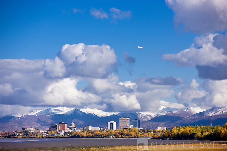 The Anchorage City Skyline and coastal mudflats seen from the Tony Knowles Coastal Trail, fall foliage, fresh snow on the Chugach mountains in the background, Anchorage, Southcentral Alaska, USA.