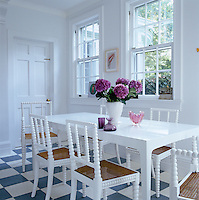 The antique English chairs in the kitchen have been painted white to match the table and the stark white decor of the room