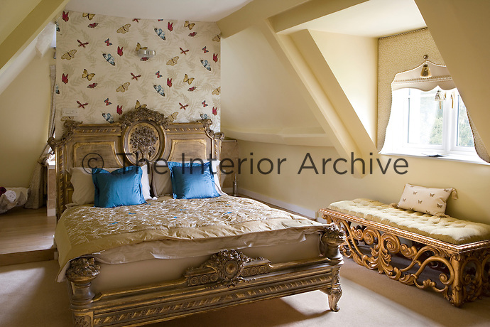 Bedroom with carved wooden double bed and butterfly print wallpaper
