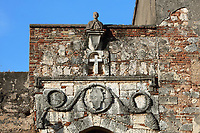 Bust, cross and reliefs above the entrance to the Monasterio de San Francisco, a monastery built 1508 by Spanish Franciscan friars, in the Colonial Zone of Santo Domingo, Dominican Republic, in the Caribbean. The complex was built under Nicolas de Ovando and it is the first monastery in the New World. The building has been repeatedly damaged by hurricanes and earthquakes and is now in ruins. Santo Domingo's Colonial Zone is listed as a UNESCO World Heritage Site. Picture by Manuel Cohen
