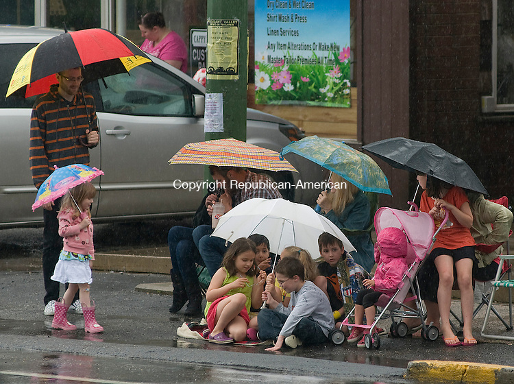 WINSTED, CT 21 MAY 2011--05211JS01----People shield themselves from the rain on Saturday prior to the start of the Winsted Rotary's 75th annual Pet Parade on Main Street in Winsted. Despite the rain, it did clear up enough for the parade to finish. <br /> Jim Shannon/Republican-American
