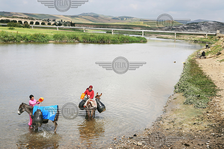 Children fetching water in the river Sebou near the village of Tlaha. The water is too polluted to be used for drinking water, as sewage from villages and towns is washed upriver, but it is used by villagers for irrigation, cleaning and livestock...