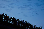 Spectators gather at dusk on Sept. 18, 2004, to watch nearly 1.5 million Mexican free-tailed bats emerge from their roosts underneath the Congress Avenue Bridge in downtown Austin, Texas and fly into the night sky.