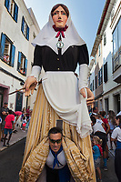 "Spain. Balearic Islands. Minorca (Menorca). Mahon. The parade of the Giants in the ""Festes de la Mare de Déu de Gràcia"" during the traditional summer festival. A man is carrying the Giant woman in the street. Maó (in Catalan) and Mahón (in Spanish), written in English as Mahon, is a municipality, the capital city of the island of Menorca, and seat of the Island Council of Menorca. The city is located on the eastern coast of the island, which is part of the autonomous community of the Balearic. In Spain, an autonomous community is a first-level political and administrative division, created in accordance with the Spanish constitution of 1978, with the aim of guaranteeing limited autonomy of the nationalities and regions that make up Spain. 7.09.2019 © 2019 Didier Ruef"