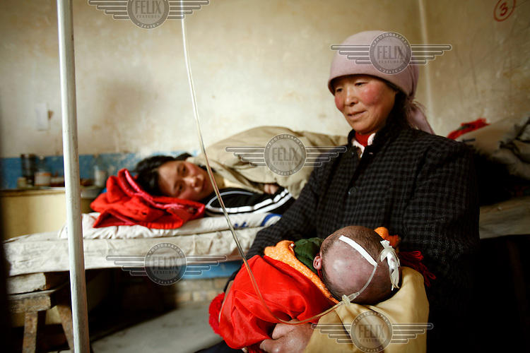 A grandmother holds her sick granddaughter, who is being treated for pneumonia, at a local clinic. The baby's mother rests on a bed nearby.