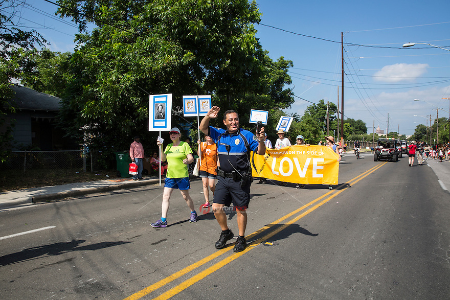 AUSTIN, TEXAS - Austin Police Chief Art Acevedo waves to the residents of East Austin while filming the event on his smartphone during the 2016 Central Texas Juneteenth Celebration Parade on Sat. June 18, 2016. <br />