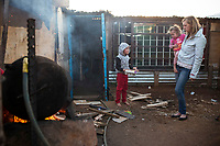 KRUGERSDORP, SOUTH AFRICA - JULY 18: Poor white Afrikaners try to stay warm during a cold day outside their family shack in Munsieville township on July 18, 2018 in Krugersdorp a suburb in Johannesburg, South Africa. This black township, where South Africans and African immigrants live, now also has a separate section of poor white Afrikaners. They live side my side but they don't mix unless they have too. Many of the residents survive by begging at traffic lights and doing odd jobs. (Photo by Per-Anders Pettersson/Getty Images)