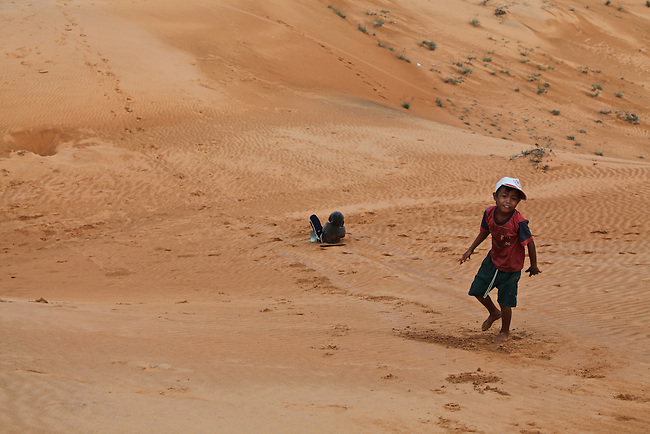 Two children demonstrate how to slide down a hill on a homemade sled at the red dunes near Mui Ne, Vietnam. Nov. 11, 2011.