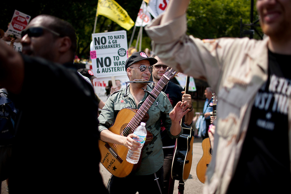 Guitarist Tom Morello, of Rage Against the Machine fame, walks through the crowd flanked by veterans after performing during a NATO Summit Protest on Sunday, May 20, 2012, at Grant Park in Chicago. (Photo by James Brosher)