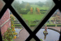 A view from one of the mullioned windows over the formal and somewhat foggy garden towards the surrounding park