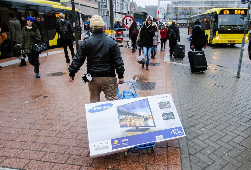 Nederland, Utrecht, 23 jan 2014<br /> Man heeft een grote platte tv gekocht en is op weg naar de bus met zijn nieuwe aankoop.<br /> <br /> Foto: Michiel Wijnbergh