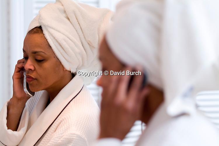 Woman wearing bathrobe, talking on cellular phone