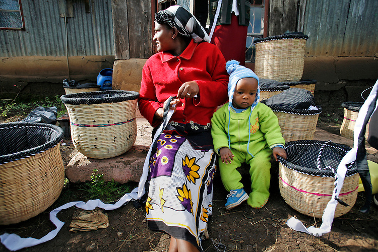 A woman with the Rurii Women's Group keeps her child nearby while hand-crafting cook baskets at a home in Kibiko, outside of Nairobi, Kenya.