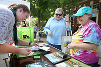 NWA Democrat-Gazette/DAVID GOTTSCHALK  Lulamae Wampler (from left), market assistant at the Fayetteville Farmers' Market, stamps Thursday, July 5, 2018, the new NWA Farmers' Market Trail passports for Carol Hill and Evevone (cq) Phillips, both of Fayetteville, at the Manager's Booth on the square in Fayetteville. Area Farmers Markets are participating in a farmers market trail where patrons have passports that are stamped when they visit participating markets. The event takes place through July and is an attempt to celebrate the diversity within the region's markets.