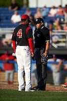 Batavia Muckdogs manager Angel Espada (4) discusses a call with umpire David Martinez during a game against the Auburn Doubledays July 10, 2015 at Dwyer Stadium in Batavia, New York.  Auburn defeated Batavia 13-1.  (Mike Janes/Four Seam Images)