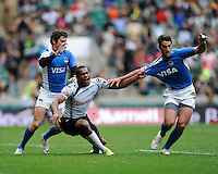 Watisoni Votu of Fiji hangs on to the shirt of Valentin Cruz of Argentina as Franco Sabato of Argentina looks on during the iRB Marriott London Sevens at Twickenham on Saturday 11th May 2013 (Photo by Rob Munro)