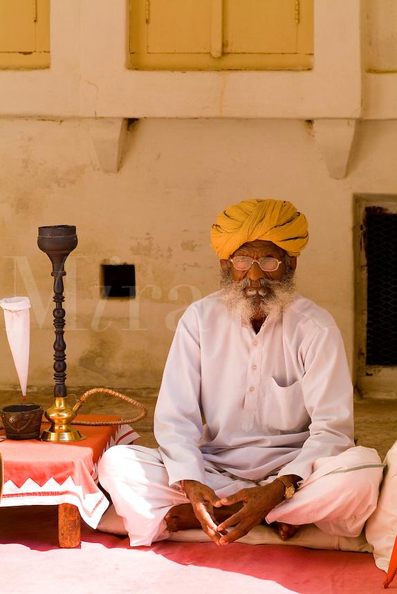 Jodhpur at Fort Mehrangarh in Rajasthan. India Hindu  man with water pipe at  doorway of Fort Palace.