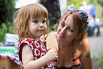 © Joel Goodman - 07973 332324 . 27 July 2013 . Hulme Community Garden Centre , Old Birley Street , Hulme , Manchester M15 , UK . Daughter Autumn Landy (two, correct) enjoys an ice lolly , watched by mother Alice Deville (correct, from Chorlton) . Hulme is Where the Art Is festival . Photo credit : Joel Goodman