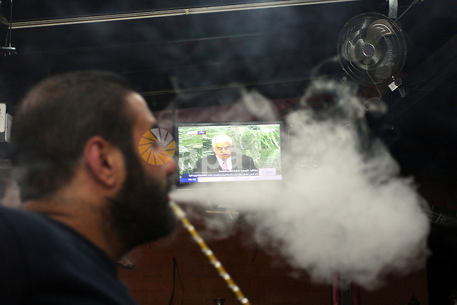 A Palestinian man smokes hookah at a cafe during the speech of Palestinian President Mahmoud Abbas at the at UN headquarters in New York in the 67th session of the United Nations General Assembly, in the West Bank city of Ramallah on 27 September 2012. Photo by Issam Rimawi