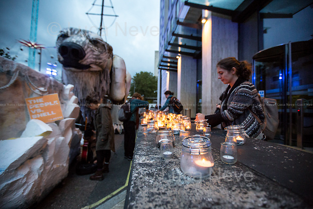 London, 20/09/2015. Today a candle-light vigil was held outside the Shell HQ in Waterloo to protest against the oil giant plan to drill the Arctic to extract oil. The demonstration was also attended by &quot;Aurora&quot;, a giant (the size of a Double Decker bus) people-powered polar bear made by Greenpeace activists. From the organiser Facebook page: &lt;&lt;The Arctic sea ice is melting. Global temperatures are rising. And yet Shell wants to drill in the Arctic's pristine environment for more of the oil that caused the ice to melt in the first place. More than 7 million people have joined the movement to save the Arctic. Two weeks ago, Aurora, a giant polar bear representing the Arctic and the strength of our movement visited Shell's HQ demanding that Shell stop drilling in her home. Two weeks down the line, Shell still refuses to pull out of the Arctic or engage in a conversation to hear out what millions have to say. Earlier this week, we heard that this year was the fourth lowest sea ice minimum on record. All the four lowest on record have happened since 2007 and scientists are telling us that this is a clear indicator of climate change. [&hellip;] live music with folk band Ys to warm your ears. [&hellip;]&gt;&gt;.<br />