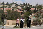 Palestinian women walk near the Jewish settlement of Beit El near the West Bank city of Ramallah on August 27, 2018. Israeli goverment approved a project to construct hundreds of new illegal Israeli settlement units in the heart of the Palestinian neighborhood of Beit Hanina, in occupied East Jerusalem, was reported to commence early next month. The illegal settlements are seen as a major obstacle to peace talks between Israel and Palestine. The Israeli settlements in occupied Palestinian territories are also regarded illegal by the international community.. Photo by Shadi Hatem