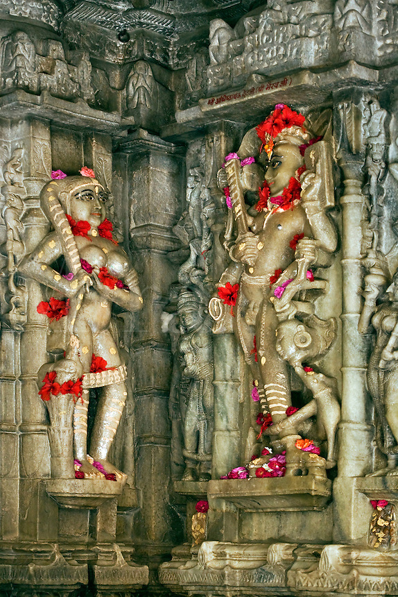 CELESTIAL DEITIES adorned with flowers inside the CHAUMUKHA MANDIR TEMPLE at RANAKPUR in the Pali District of RAJASTHAN near Sadri - INDIA