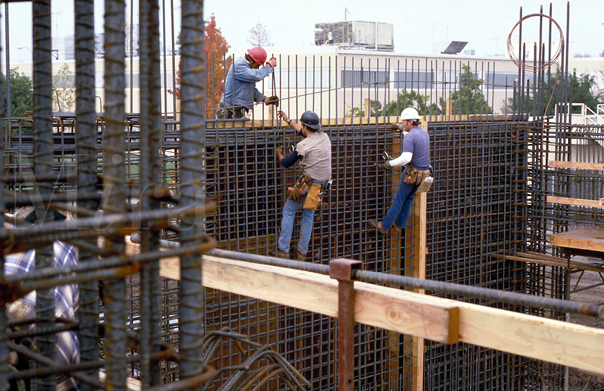 Workers reinforcing steel frame for concrete construction. occupations. California.