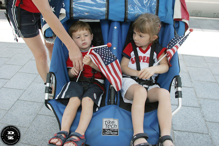 USA National Soccer Team fans Zackary Zaman 2 1/2 years old, and Dezirae Zaman, 4 1/2 years old,  are handed a flag from their mother Lynn  while their father Jeff gets ready to push them from the Kaiserslautern train station.  They arrived early before their FIFA World Cup First round match against Italy on Saturday June 17th, 2006 in Kaiserslautern, Germany.  The USA and Italy tied 1-1