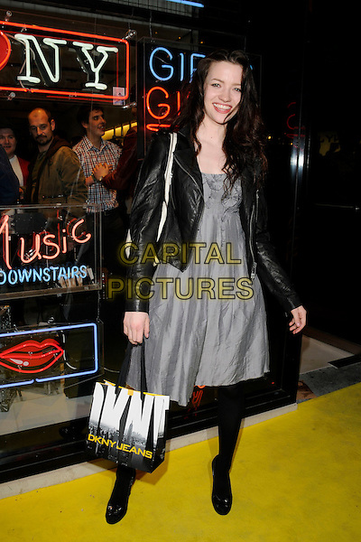 TALLULAH RILEY.DKNY Jeans Flagship Store launch party, 124 New Bond Street, London, England..April 10th, 2008.full length black leather jacket tights grey gray dress goody bag.CAP/CAN.©Can Nguyen/Capital Pictures.