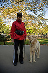 Woman standing next to white Standard Poodle, looking at each other in Central Park, NYC