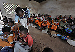 """The teacher supervises students' work in a primary school class in Chidyamanga, a village in southern Malawi that has been hard hit by drought in recent years, leading to chronic food insecurity, especially during the """"hunger season,"""" when farmers are waiting for the harvest."""