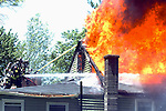 Firefighters in Stafford (I'm not sure I think these are Tolland guys) work from the lower roof as the pour water on the upper portion of a home heavily involved in flames, Wednesday, June 11, 2008,  on Crystal Lake Rd in Stafford. The West Stafford Fire Dept. was assisted by Crystal Lake, Staffordville, Tolland and Somers for tankers and manpower and Vernon for their air supply truck, no injuries were reported but the multi-family home was gutted in the blaze. (Jim Michaud/Journal Inquirer)