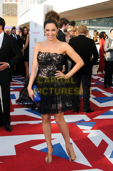 Kelly Brook.Arrivals at the Arqiva British Academy Television Awards held at the Royal Festival Hall, London, England..May 27th, 2012.BAFTA BAFTAS full length black dress hand on hip lace tulle strapless blue clutch bag.CAP/CJ.©Chris Joseph/Capital Pictures.