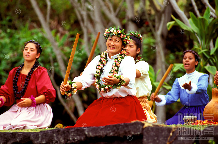Women wearing colorful traditional costumes and adorned with lei and haku lei (floral headpiece) perform hula kahiko at Hawaii Volcanoes National Park on the Big Island of Hawaii.