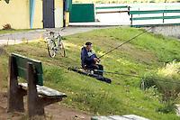 Man fishing in City lake with his bicycle. Rawa Mazowiecka Central Poland