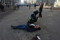 A policeman provides first aid to a wounded protesters that fell on the field.  Kiev, Ukraine