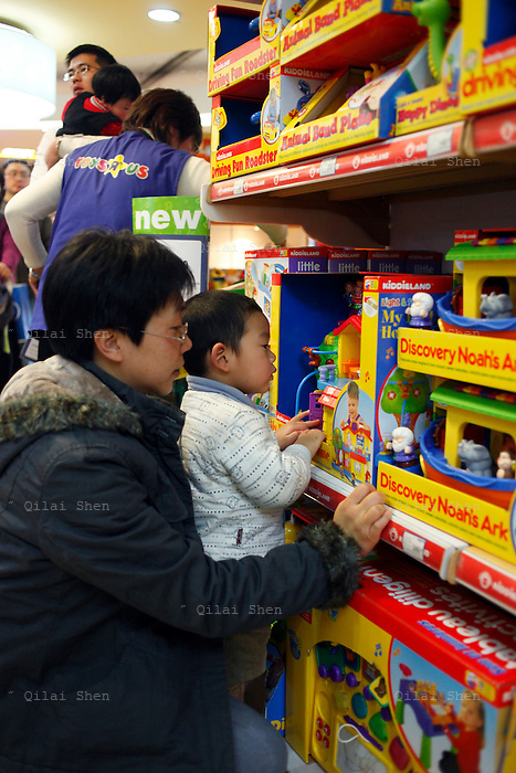 Parents take their children to shop for  toys at a Toys R Us store in Shanghai, China on 28 January 2009.