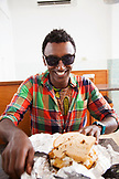 BERMUDA. St. George. Chef Marcus Samuelsson about to eat a fish sandwich at Art Mel's Spicy Dicy Restaurant in St. George.