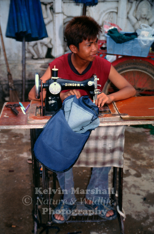 Young Thai tailor using his sewing machine on a busy street. Bangkok - Thailand.