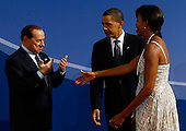 Pittsburgh, PA - September 24, 2009 -- United States President Barack Obama (C) and U.S. first lady Michelle Obama (R) welcome Italian Prime Minister Silvio Berlusconi to the welcoming dinner for G-20 leaders at the Phipps Conservatory on Thursday, September 24, 2009 in Pittsburgh, Pennsylvania. Heads of state from the world's leading economic powers arrived today for the two-day G-20 summit held at the David L. Lawrence Convention Center aimed at promoting economic growth.  .Credit: Win McNamee / Pool via CNP