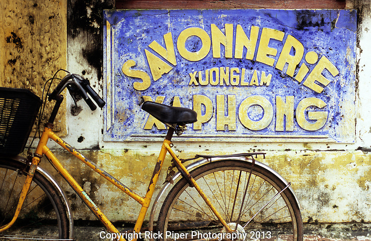 Bicycle 01 - Old weathered Savonnerie Xuong Lam Xa Phong sign and yellow bicycle, in Nguyen Thai Hoc St, Hoi An, Viet Nam