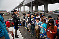 Job seekers from the countryside arrive on the edge of Chongqing city to apply for work at the Foxconn factory. The workers, mostly children of farmers, are part of a generation that is quickly urbanizing. They are being picked up at the light rail station for interview at Apple's contract factory. If they succeed, they would land jobs making Apple products including the iPhone. Foxconn hit the news last year when it was rocked by a series of workers' suicide. The Chinese government plans to move 250 million rural residents into urban areas over the coming dozen years though it is unclear whether people want to move and where the money for this project will come from. Further urbanisation is meant to drive up consumption to counterbalance an export orientated economy and end subsistence farming but the drive to get people off the land is causing tens of thousands of protests each year. /Felix Features