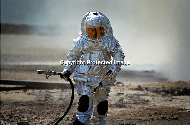 An unidentified firefighter walks with a protective suit while putting out oil wells on fire on August 9, 1991, at Greater Burhan oilfield in Kuwait. When the Gulf War ended in February 1991, the Iraqi forces retreated and hundreds of wells were blown up. Expert teams mainly from USA and Canada arrived and the last fires were put out in October 1991.