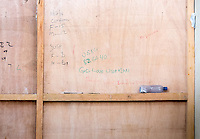 """God love Liberian"" is written on the wall in the doffing area. Old notes that indicate suspected and confirmed Ebola cases can be seen as well. Occidental College professor Mary Beth Heffernan works on her PPE Portrait Project with health care workers at the ELWA II ETU (Ebola treatment unit) in Monrovia, Liberia on Saturday, March 8, 2015.<br /> (Photo by Marc Campos, Occidental College Photographer) Mary Beth Heffernan, professor of art and art history at Occidental College, works in Monrovia the capital of Liberia, Africa in 2015. Professor Heffernan was there to work on her PPE (personal protective equipment) Portrait Project, which helps health care workers and patients fighting the Ebola virus disease in West Africa.<br />