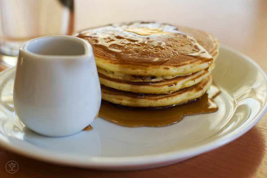 A stack of three pancakes with syrup and a syrup jug on a white plate at a breakfast cafe.