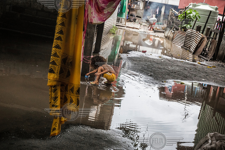 A child plays in a puddle between houses in Lord Howe Settlement, which gets flooded after every heavy rain storm.  Lord Howe Settlement, a district of the capital Honaria, is populated by people from Ontong Java Atoll (AKA Lord Howe Atoll), a Polynesian outlier of the Solomon Islands. Its people have been moving to Lord Howe Settlement in search of a better life since the 1970s. Climate change leading to rising sea levels and consequent food insecurity now means the atoll is existentially threatened. The remaining Ontong Javanese people are considering the possibility of complete relocation to Santa Isabel Island and to Honiara. However, with Lord Howe Settlement itself suffering the consequences of extreme weather and overcrowding, community leaders believe it is not a viable long term home. Furthermore, they fear that the Ontong Javanese people's Polynesian identity will be lost as a new generation is brought up in a location with no connection to ancestral land. Their identity will be weakened as they become a minority amongst Melanesian communities that have vastly different traditions and speak different languages.